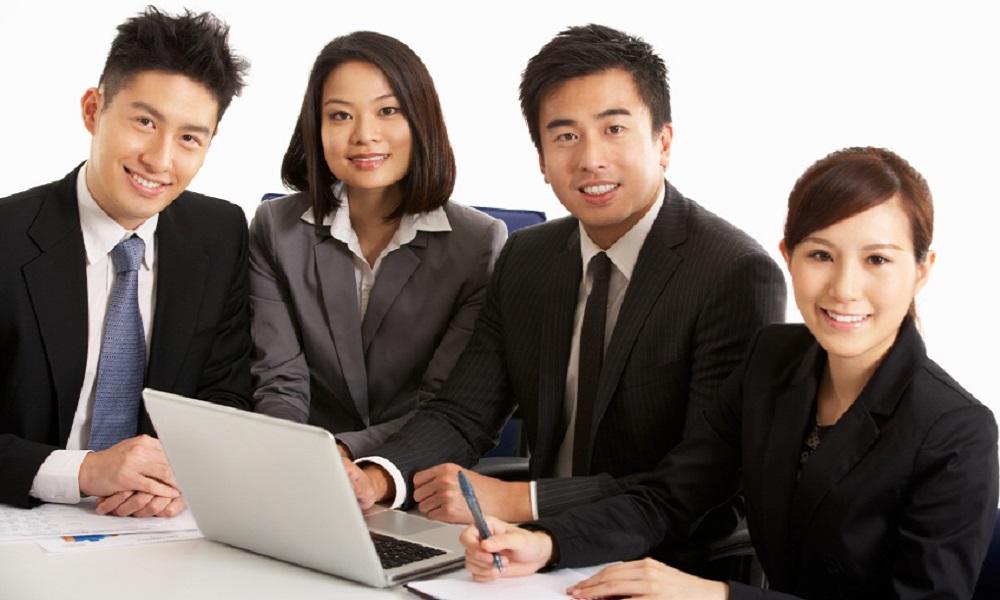 Studio Shot Of Chinese Businesspeople Having Meeting